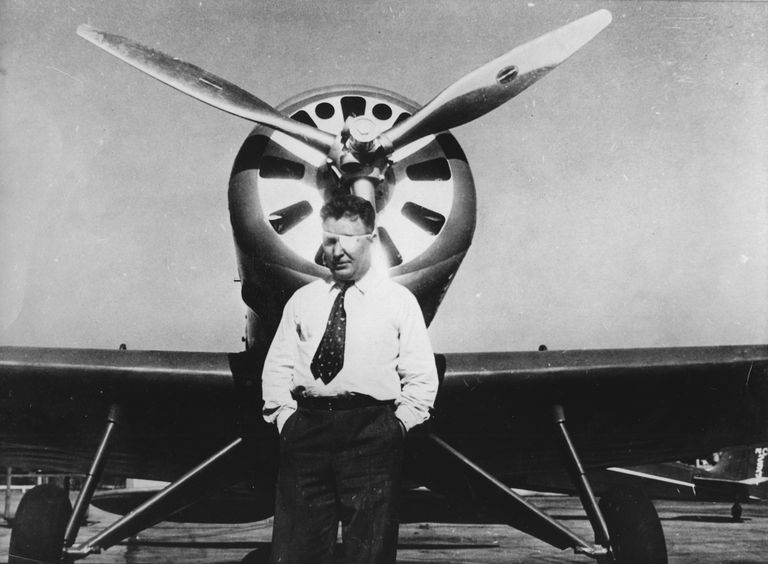 Famous aviator Wiley Post in front of his airplane.