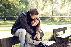 Young couple sitting on bench outdoor.