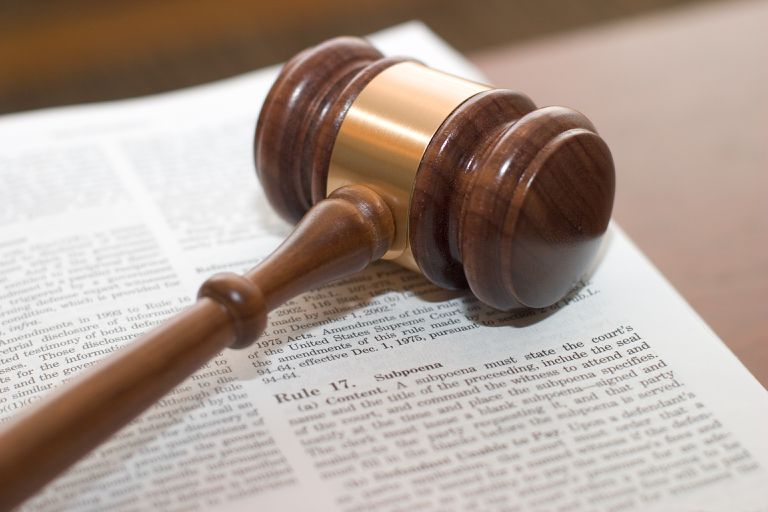 A gavel on top of an open book that shows a rule concerning subpoena.