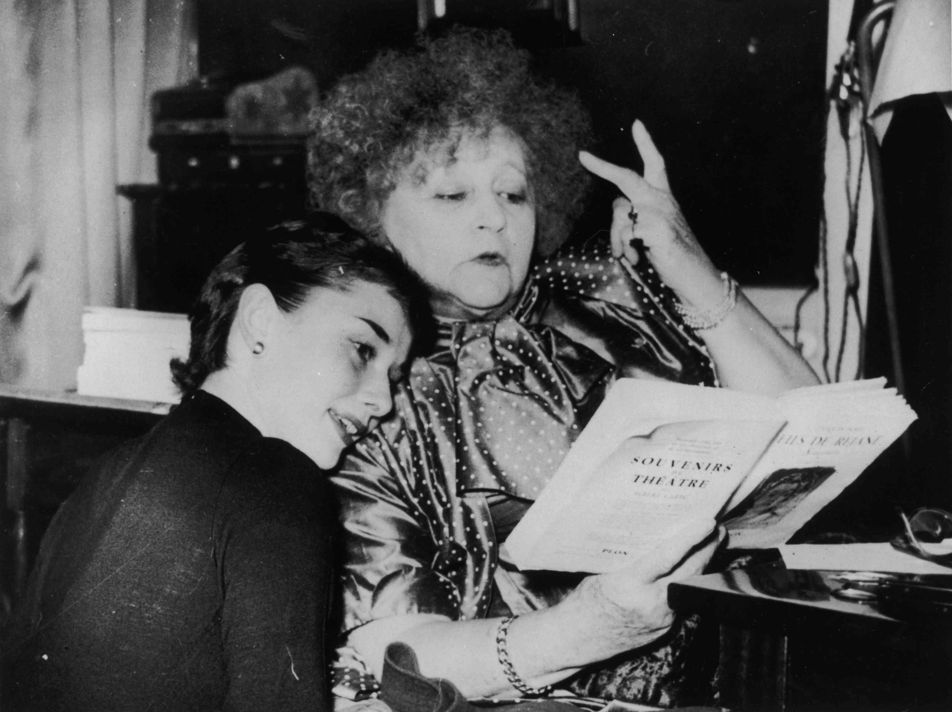 Colette lee un guión mientras Audrey Hepburn se inclina sobre ella y lee por encima del hombro