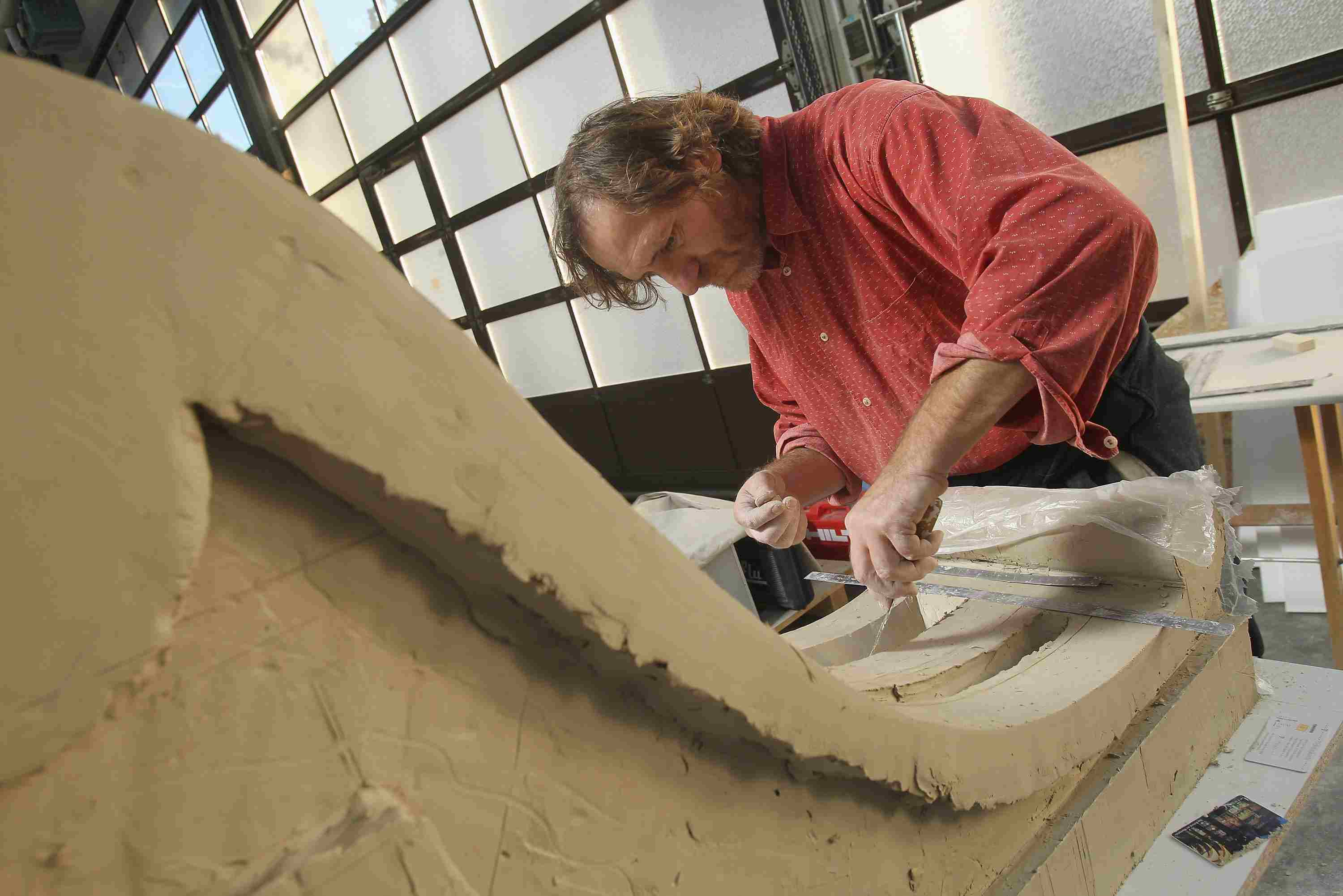 man in red shirt sculpting a large corbel from clay