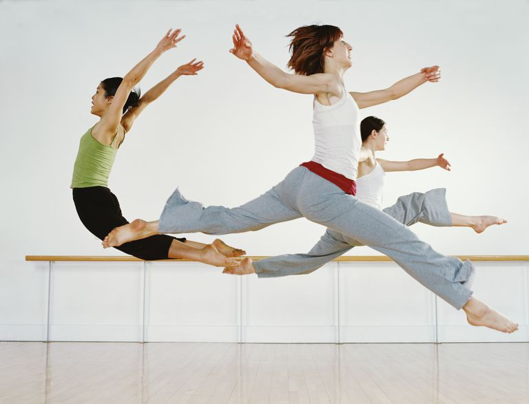 Three female dancers practicing in dance studio, leaping