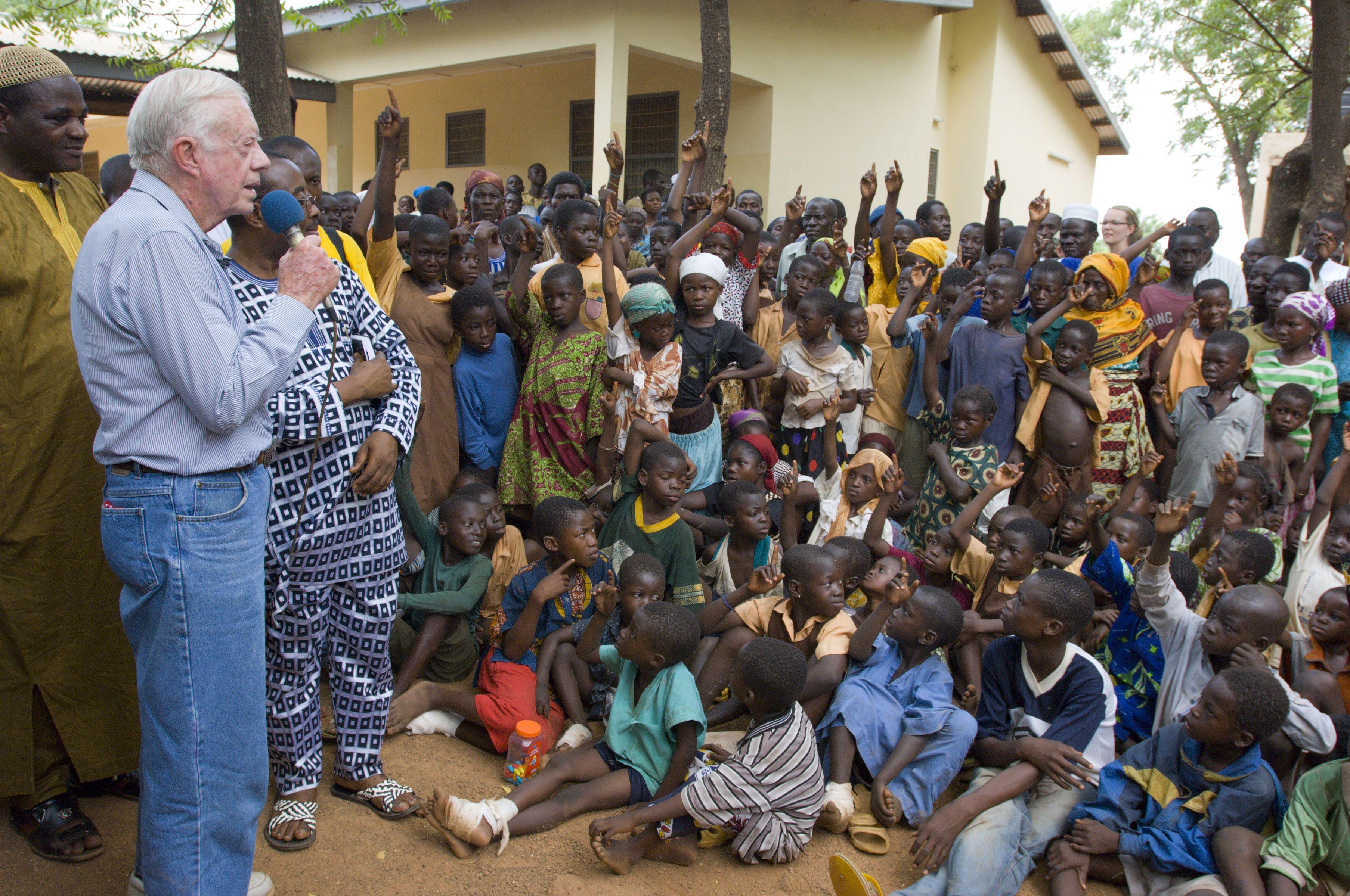 Former U.S. President Jimmy Carter talking to Ghanaian children about Guinea worm disease.