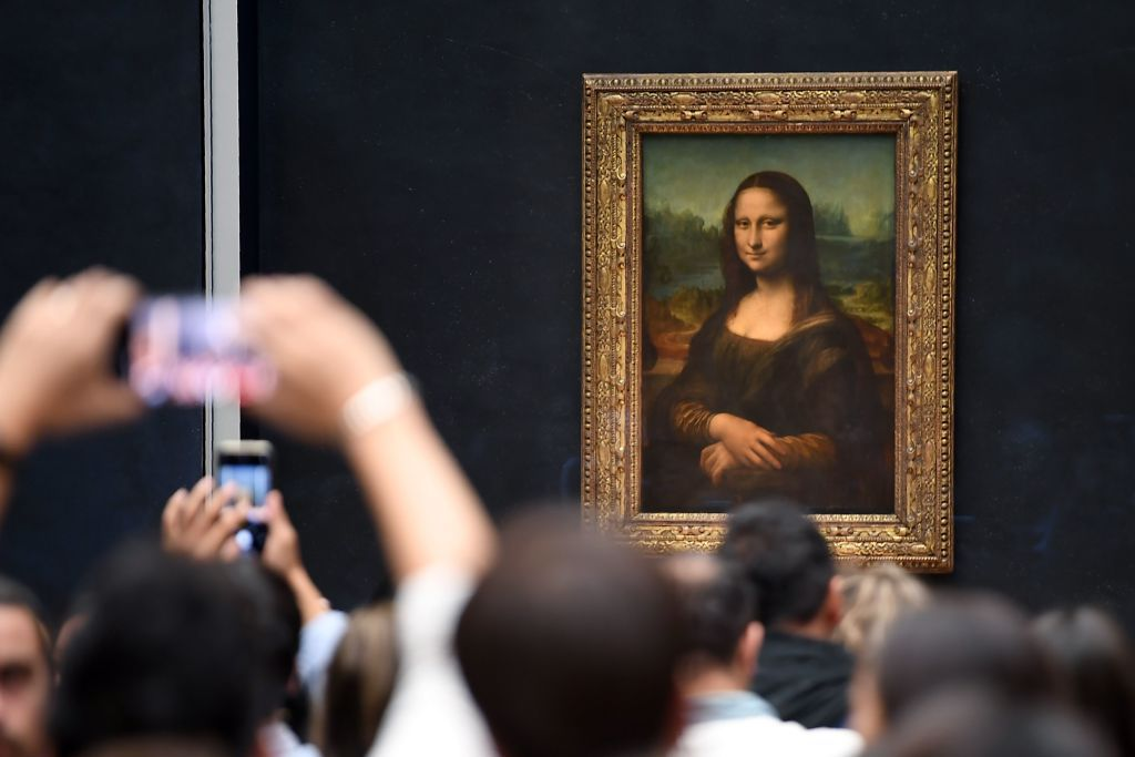 Visitors take pictures in front of the Mona Lisa