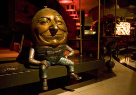A metal sculpture of Humpty Dumpty sitting on a bench