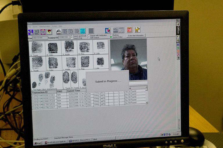 Pantalla de computadora mostrando foto de migrante y huellas digitales.
