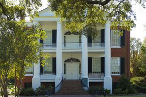 4 Tuscan Columns rise to pediment over two front porches on a brick, 2-story building with black shutters