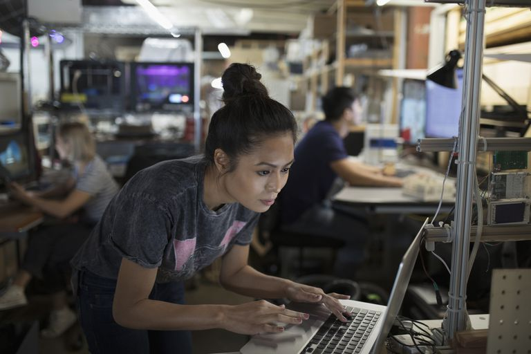Focused female engineer working at laptop in workshop