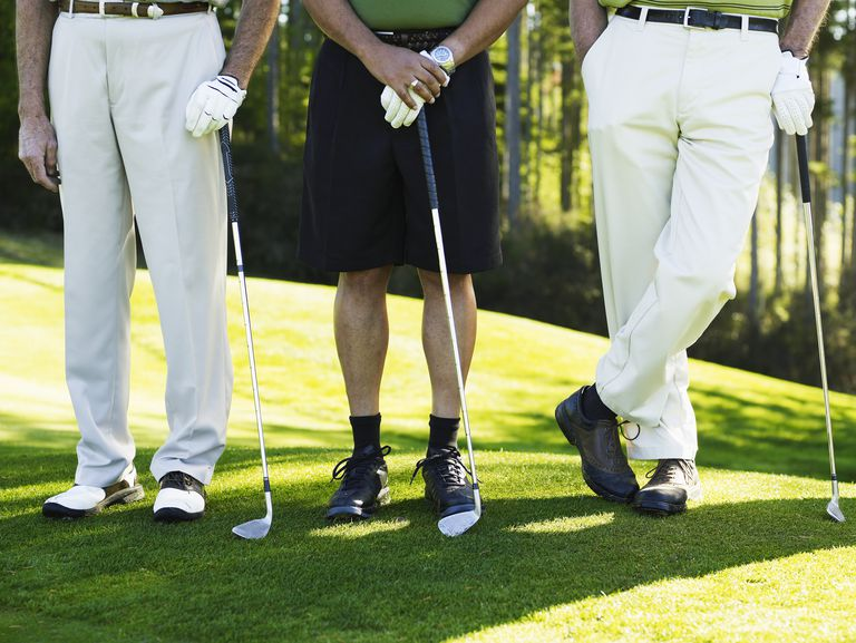 Three golfers, one wearing shorts