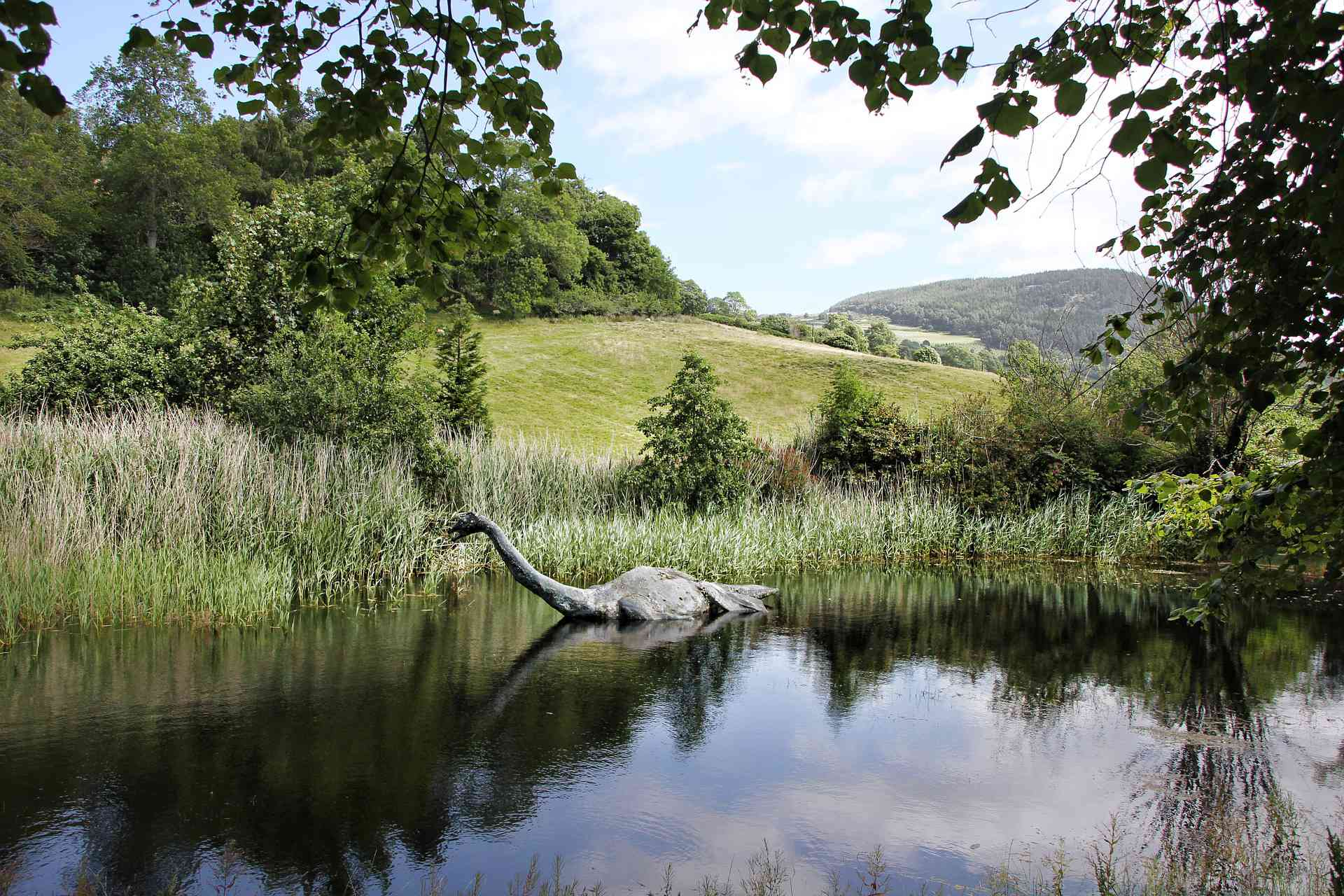 Statue of the Loch Ness Monster floating in a lake.