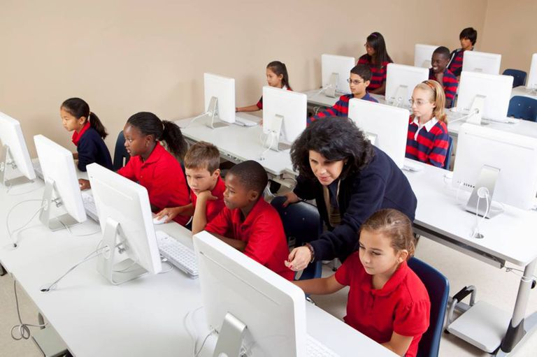 Teaching helping students sitting at computers in classroom