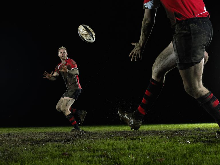 Two male rugby players passing ball on field