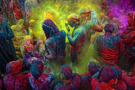 People smear each other in colored paint in celebration of Holi, a Hindu festival