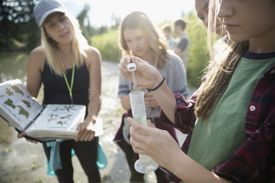 Teacher and teenage girls performing experiments outside.