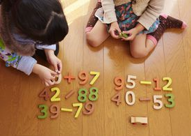 two young girls playing with number blocks