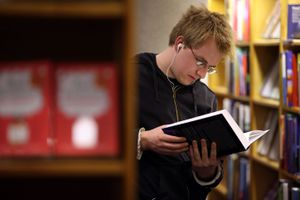 Student Reading Book in a library