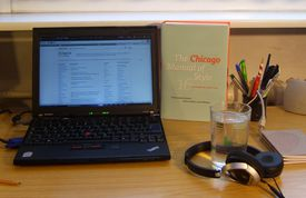 Desk with a laptop and a style guide book with various clutter nearby.