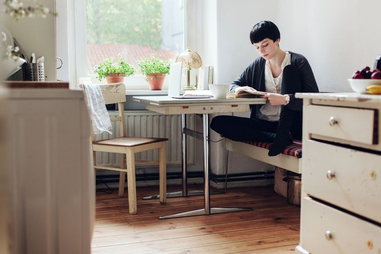 Person Reading A Book In Her Kitchen.