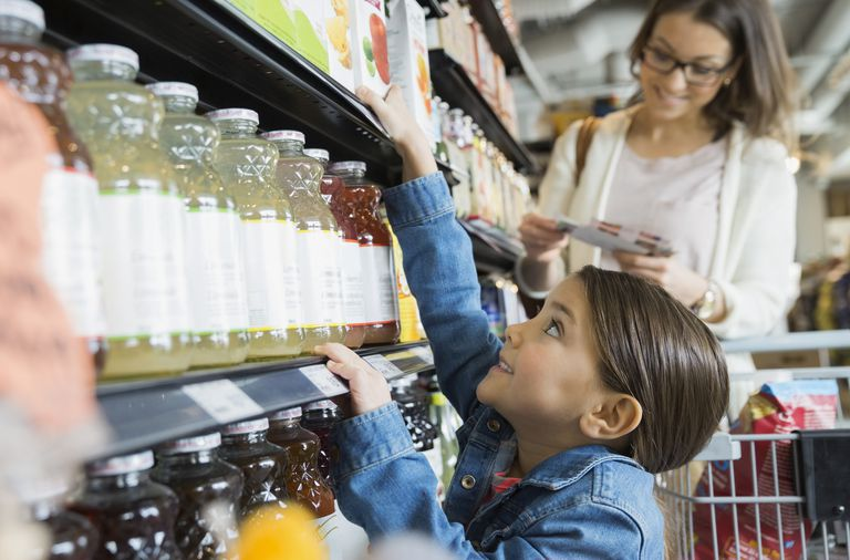 Girl reaching for juice on shelf in market