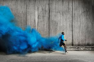 Athlete with trail of blue smoke