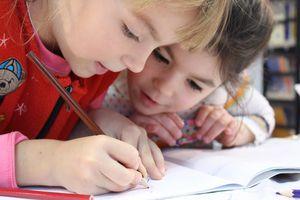 two young girls writing