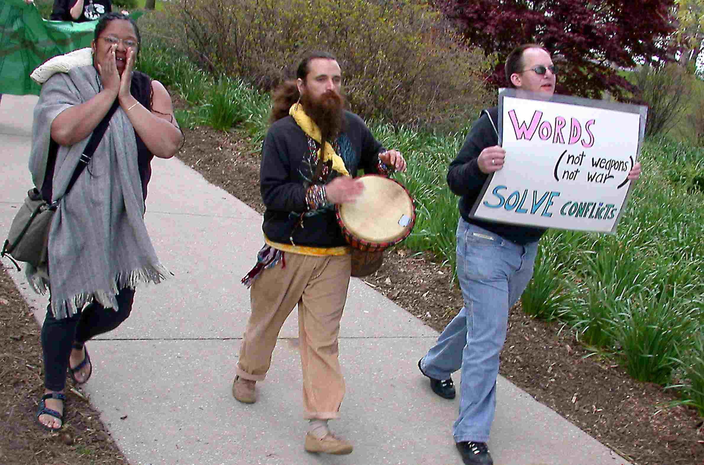 A woman shouts, a bearded man plays a drum, and another man holds a protest sign.