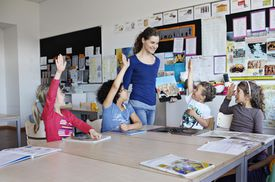 Teacher with class of kids with raised hands