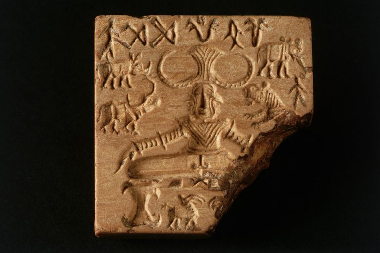Stone engraving from the Indus Valley of a person sitting surrounded by animals