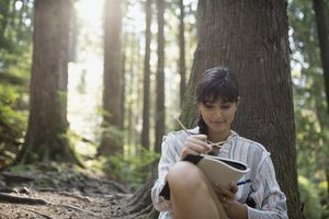 A woman writing in a journal in the woods.