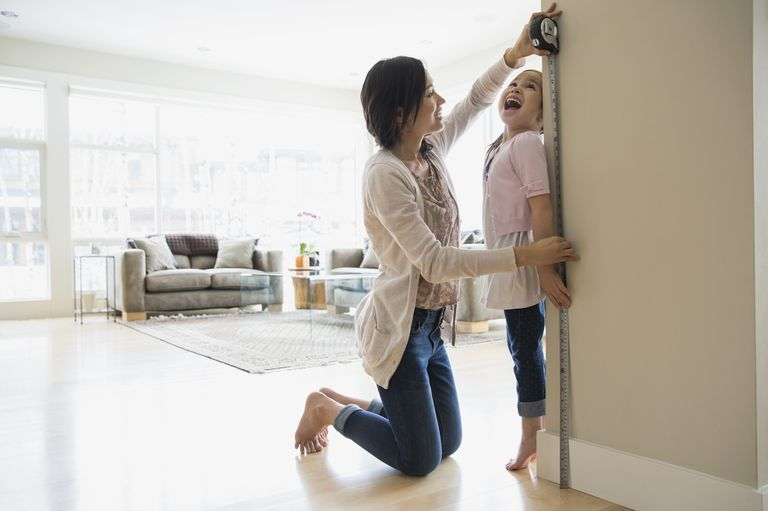 Mother measuring her daughter's height against a living room wall.