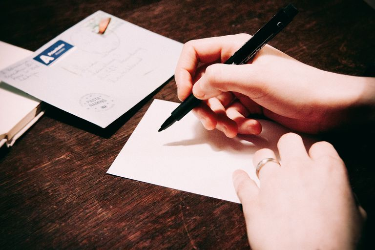 Person writing on a postcard