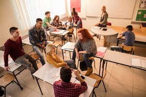 Above view of students communicating during break in the classroom.