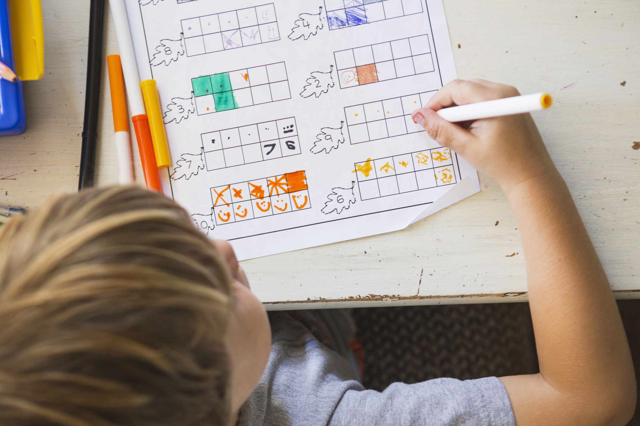 A boy coloring in a math worksheet.