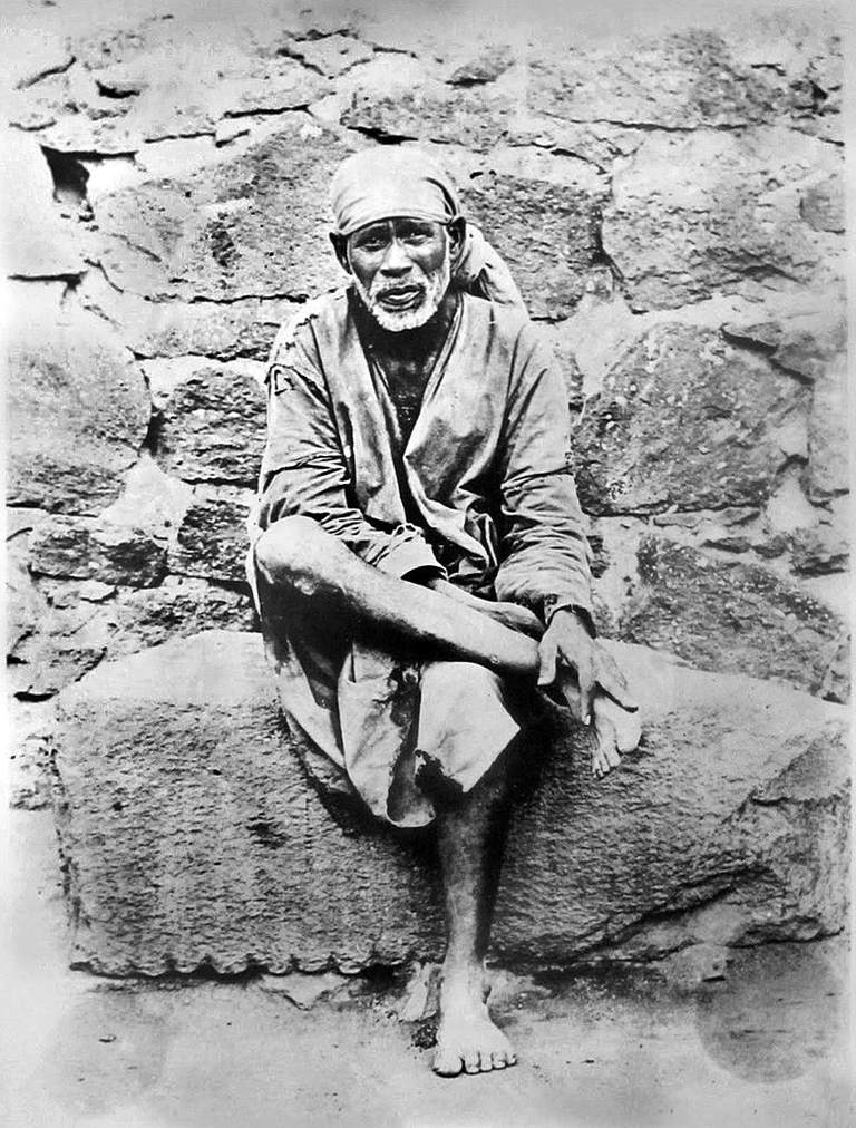 Portrait of Sai Baba sitting on a rock in front of stone wall.