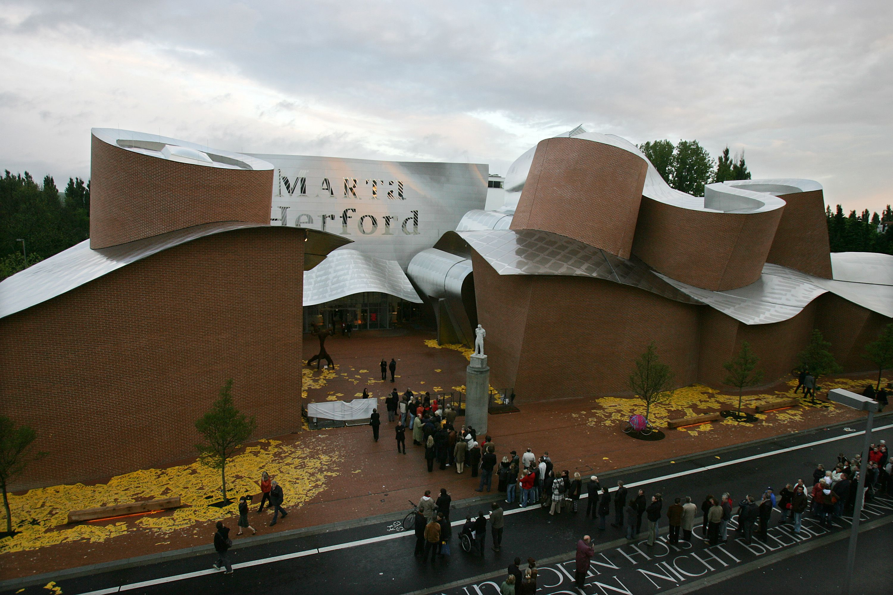 long view of wavy metal roof on red brick building named MARTa Herford -- People line up to enter the 'MARTa' museum on May 7, 2005 in Herford, Germany. The museum of contemporary art and design, designed by US star architect Frank Gehry, offers an exhibition space of 2,500 square meters and was completed after a construction time of four years.