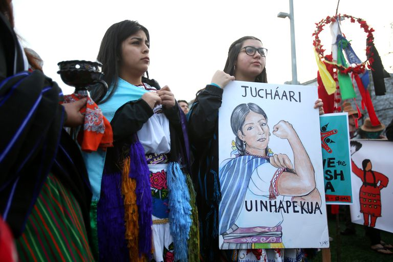 Two Mexican activists holding a poster with an image of an Indigenous woman in the style of Rosie the Riveter