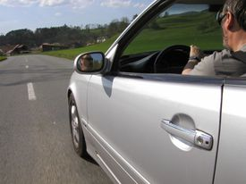A driver in a car on a road through the countryside