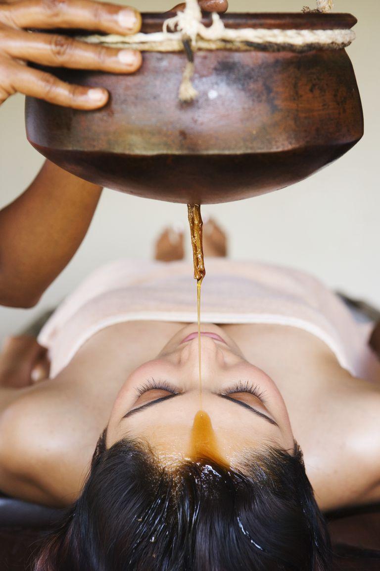 Woman receiving shirodhara therapy