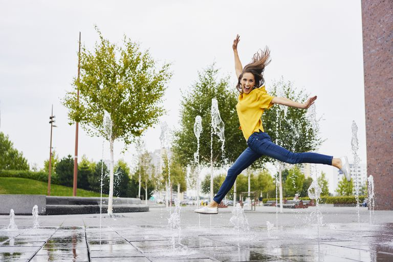 Woman jumping in a water feature