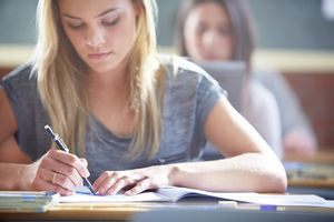 Female student in classroom writing at desk