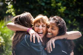 Women greeting one another with a warm embrace