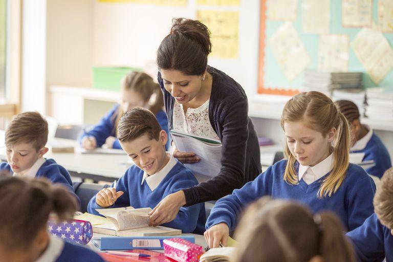 A teacher helps a boy in an elementary school classroom