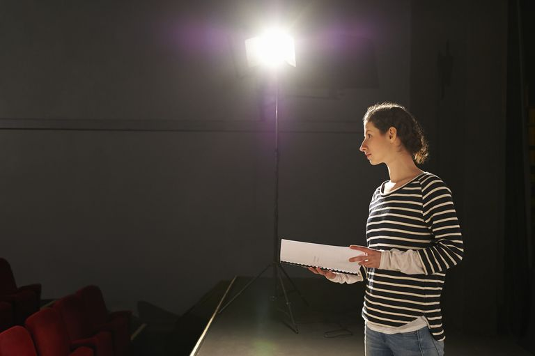 Profile of actress under spotlight on stage.
