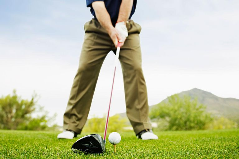 Male golfer preparing to hit tee shot