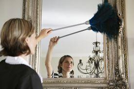 maid dusts ornate mirror