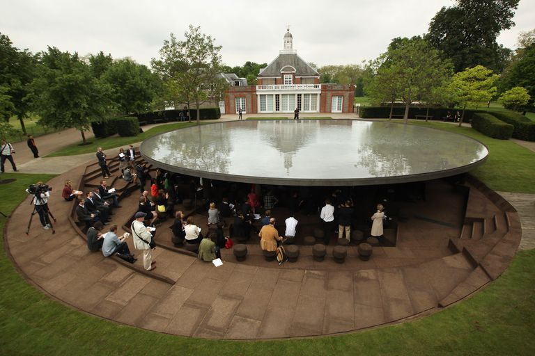 modern, round stone flat roof with sunken multi-level gathering space underneath, a brick British building in the background