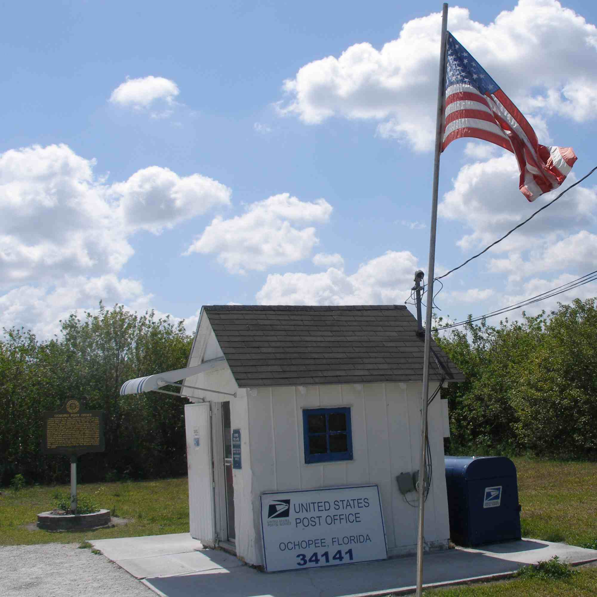 Photo of small, white building, postal boxes, sign, U.S. flag, and historical marker.