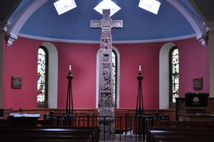 An ornate carved stone cross at the center of a domed church building.