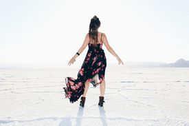 A woman with her back to camera standing alone on Bonneville Salt Flats