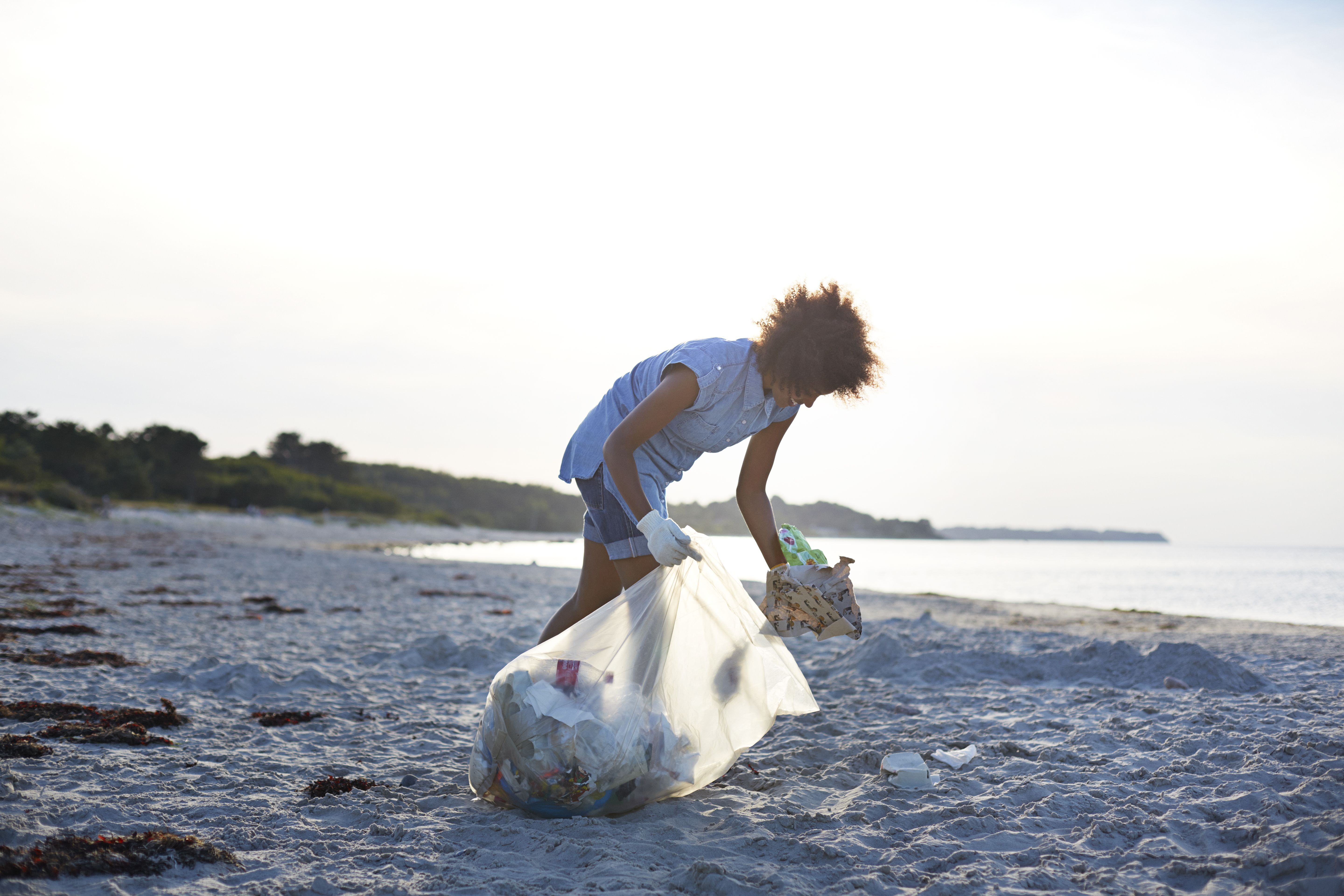 Young woman collecting trash on beach